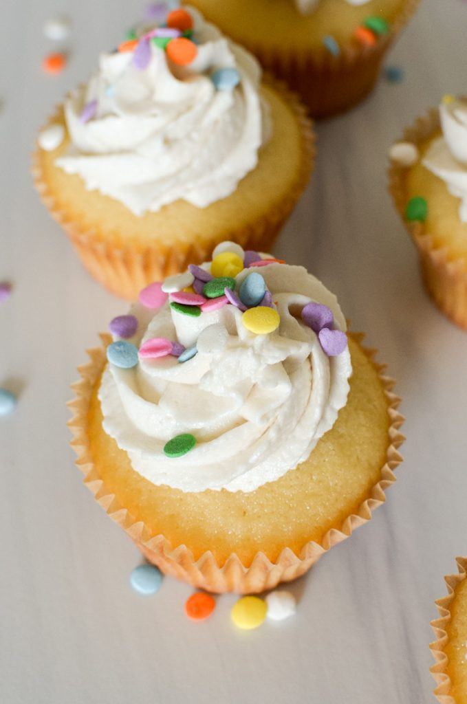 Overhead of frosted yellow cupcakes