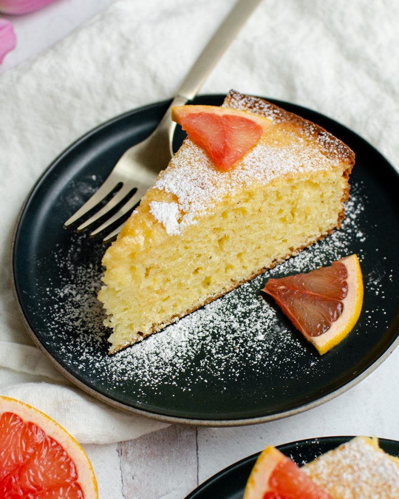 Fresh Grapefruit Cake Slice on a plate with extra grapefruit