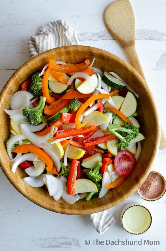 Raw fajita veggies in a large wooden mixing bowl