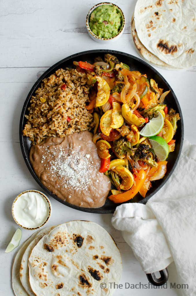 Fajita veggies served on a skillet with rice, beans, and tortillas.
