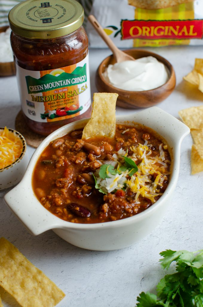 Game Day Chili with salsa in a bowl topped with cheese and onions