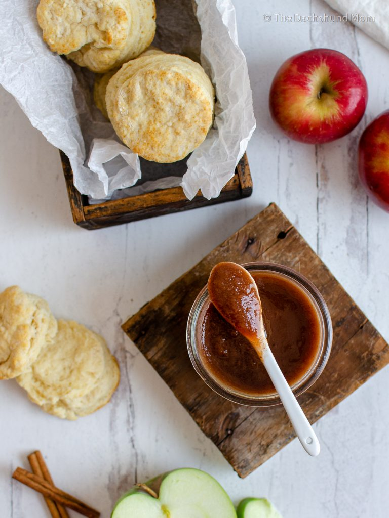 Homemade apple butter on a table with homemade biscuits and fresh apples